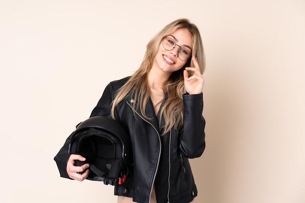 Donna con un casco del motociclo isolato sulla parete beige con gli occhiali e felice