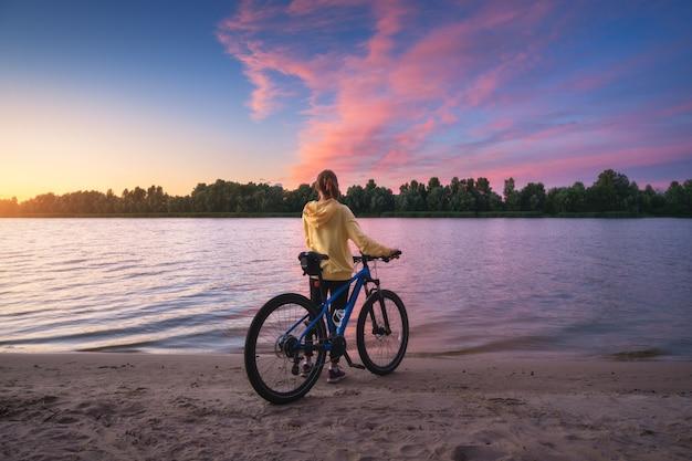 Donna con mountain bike sulla costa del fiume al tramonto in estate. paesaggio con ragazza, bicicletta, spiaggia sabbiosa, cielo viola con nuvole rosa colorate, acqua al tramonto. sport e viaggi. ciclo. natura