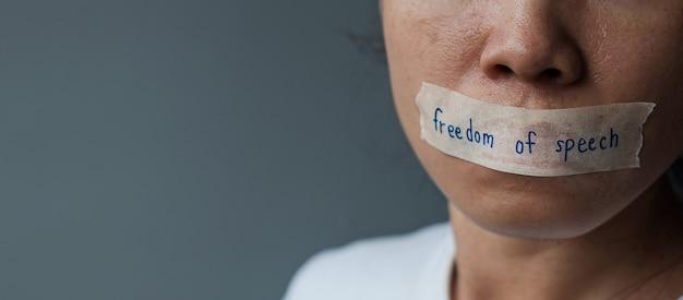 Donna con la bocca sigillata in nastro adesivo con messaggio di libertà di parola, libertà di stampa, diritti umani, dittatura di protesta, democrazia, libertà, uguaglianza e concetti di fraternità