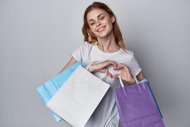Donna con borse della spesa multicolori sfondo chiaro di stile di vita da maniaco dello shopping