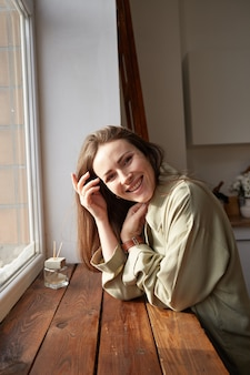 Donna con le lentiggini naturali che gode della luce solare di mattina sulla cucina nella sua casa di eco.