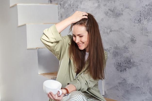 Donna con le lentiggini naturali che si gode la luce del sole del mattino mentre è seduto sulle scale di casa sua.