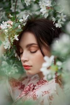Donna con trucco naturale, cosmetici floreali per la pelle del viso, ragazza in posa su rami di fiori di melo in fiore in primavera