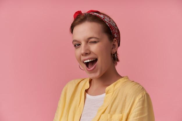 Donna con trucco naturale che indossa una maglietta bianca e una maglietta gialla e una bandana rossa in posa sul muro rosa emozione che ti guarda occhiolino flirtare sorridente