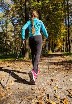 Donna con bastoncini da nordic walking sul parco