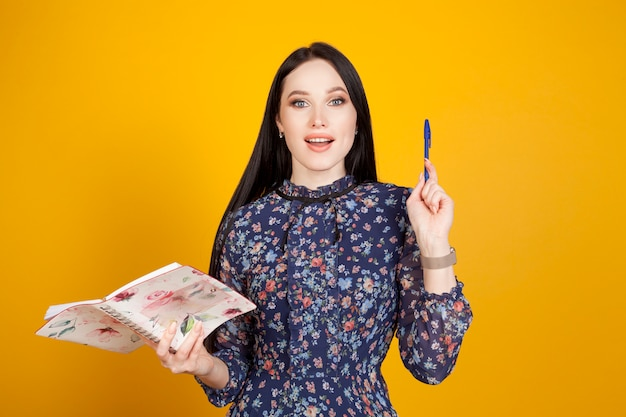 Una donna con un blocco note e una penna sollevata, su uno sfondo giallo, con un'emozione di ispirazione. il concetto dell'idea.