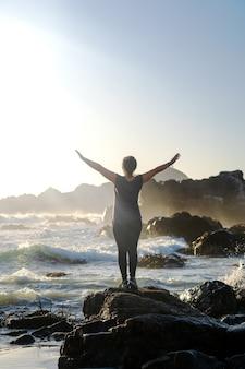 Donna con le braccia aperte sulla spiaggia al tramonto sentendosi felice e libera nella natura