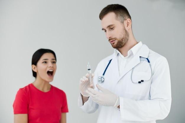 Donna con la bocca aperta ha paura delle iniezioni vicino al medico.