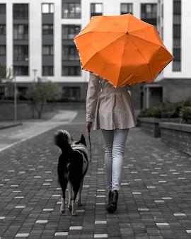 Donna con un ombrello arancione cammina con un cane in città