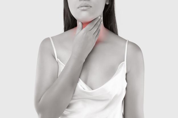 Una donna con un dolore alla gola. mal di gola a causa dell'epidemia di virus.