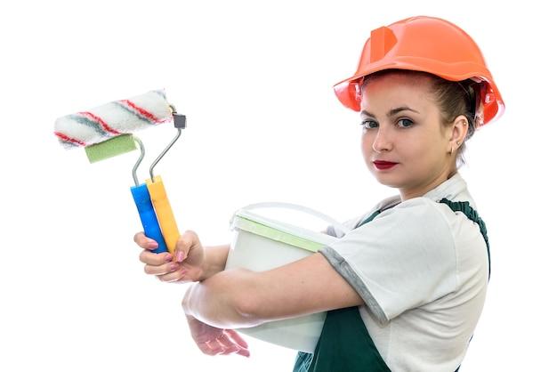 Donna con vernice nel secchio e strumenti isolati su bianco