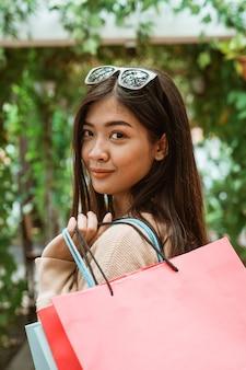 Donna con i sacchi di carta che gode della compera