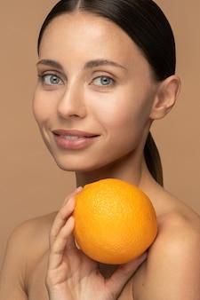 Donna con la pelle del viso perfetta, capelli pettinati, tenendo l'arancio.
