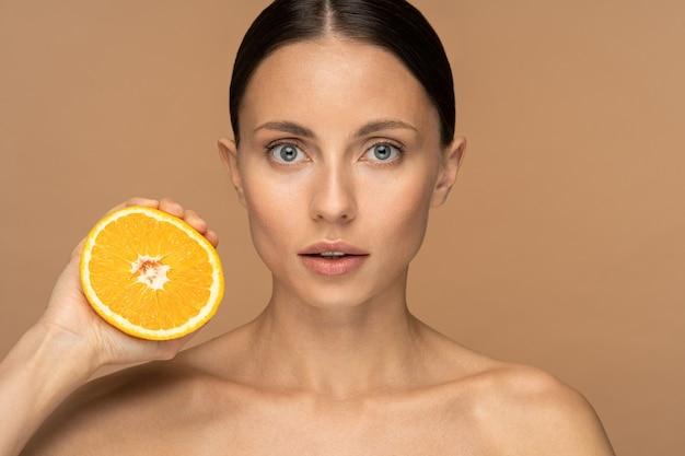Donna con la pelle del viso perfetta, capelli pettinati, spremitura di arancia.