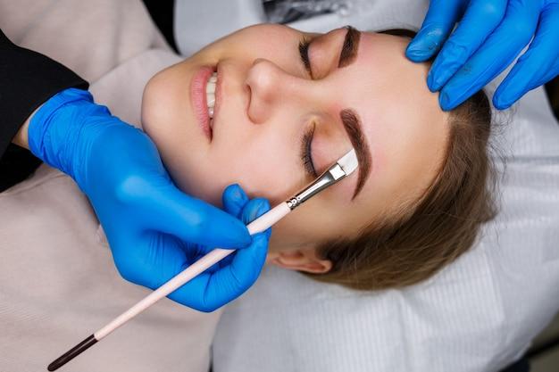 Donna con il tatuaggio permanente di trucco sulle sue sopracciglia. l'estetista del primo piano fa uno schizzo delle sopracciglia. trucco professionale e cura della pelle cosmetica.