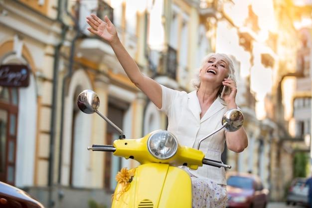 Donna con telefono su scooter.