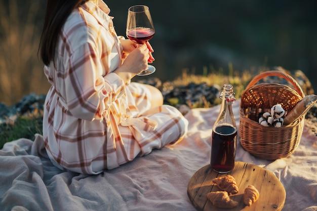 Donna con cestino da picnic che beve vino