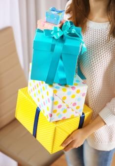 Donna con una pila di regali a casa, primo piano