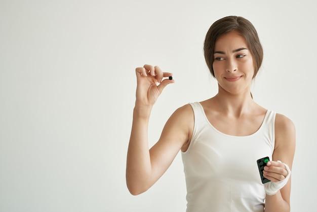 Donna con le pillole in mano in maglietta bianca ferita medicina per la salute della mano