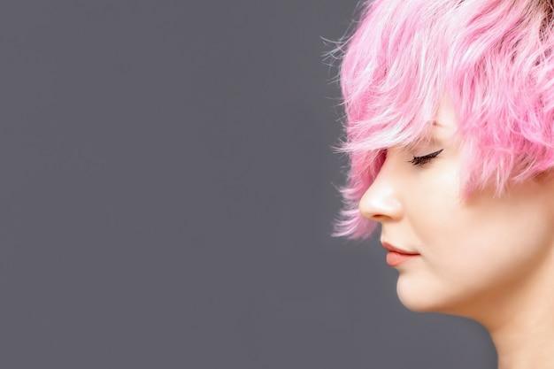 Donna con acconciatura rosa sta con vista laterale gli occhi chiusi