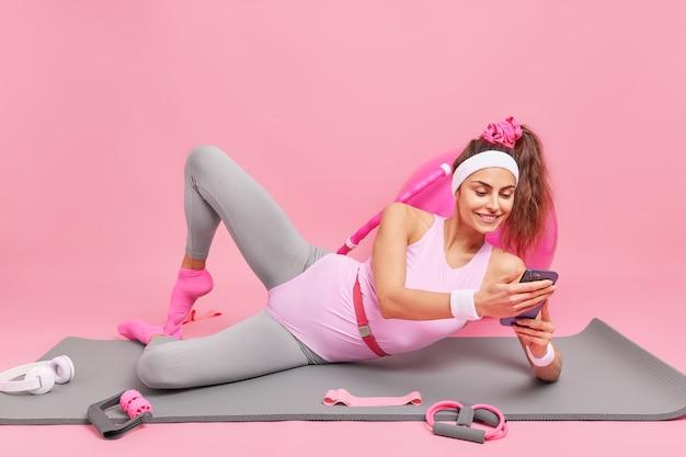 Donna con coda di cavallo vestita con abiti sportivi si trova sul tappetino fitness dopo l'esercizio preferisce uno stile di vita sano invia messaggi di testo sullo smartphone utilizza attrezzature sportive