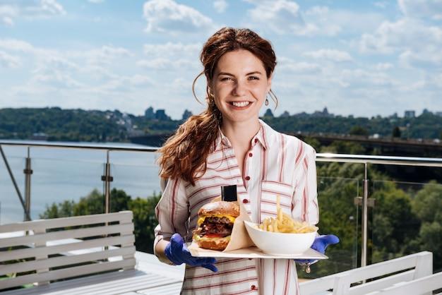 Donna con coda di cavallo. donna sorridente con la sensazione di coda di cavallo riposata mentre si mangia patate e hamburger di carne