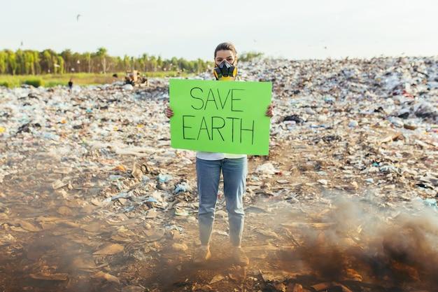 Donna con un poster salva il pianeta, picchetti in un ambiente contaminato da rifiuti, fuoco ardente e fumo nero