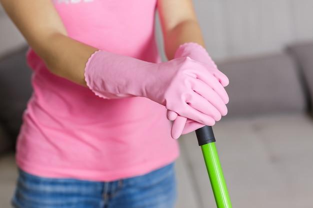 Donna con guanti protettivi utilizzando una scopa per pulire il pavimento