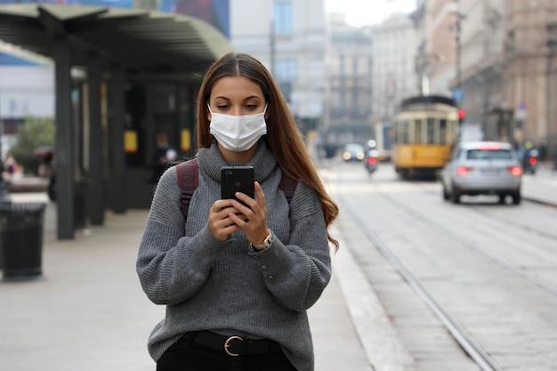 Donna con maschera protettiva che acquista e paga il biglietto di trasporto online tramite l'app bancaria