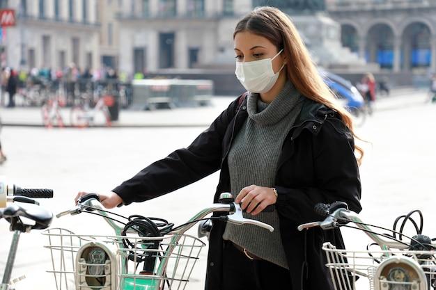 Donna con maschera protettiva prendendo una bicicletta in una piattaforma di bike sharing