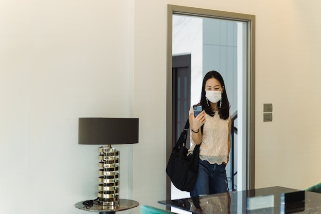 Donna con videochiamata maschera protettiva sul cellulare