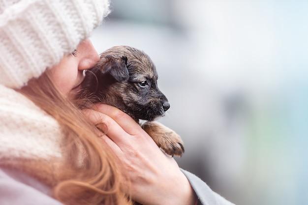 Donna con cucciolo su uno sfondo con bokeh defocus.