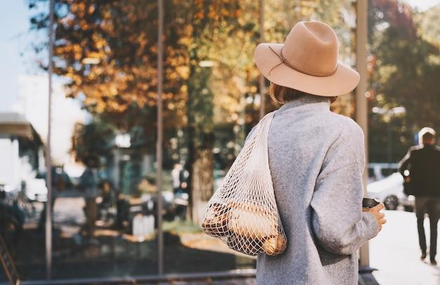 Donna con acquisto in sacchetto di rete riutilizzabile di cotone e tazza di vetro sulla vetrina di un negozio a rifiuti zero