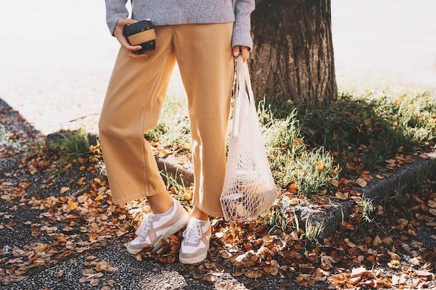 Donna con acquisto in sacchetto di rete riutilizzabile in cotone sullo sfondo del negozio di rifiuti zero shop
