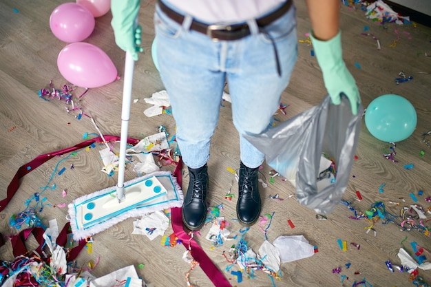 Donna con il disordine pulizia pushbroom del pavimento in camera dopo i coriandoli di festa, la mattina dopo la celebrazione della festa, i lavori domestici, il servizio di pulizia