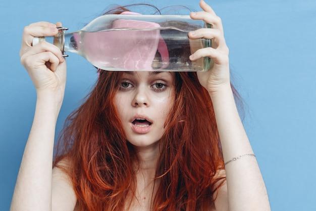 Donna con capelli rossi bottiglia alcol postumi di una sbornia maschera di sonno sfondo blu. foto di alta qualità