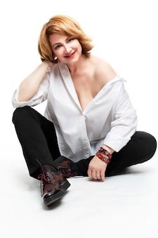 Una donna con i capelli rossi in una camicia bianca si siede e sorride. invecchiamento bello e felice. . verticale.