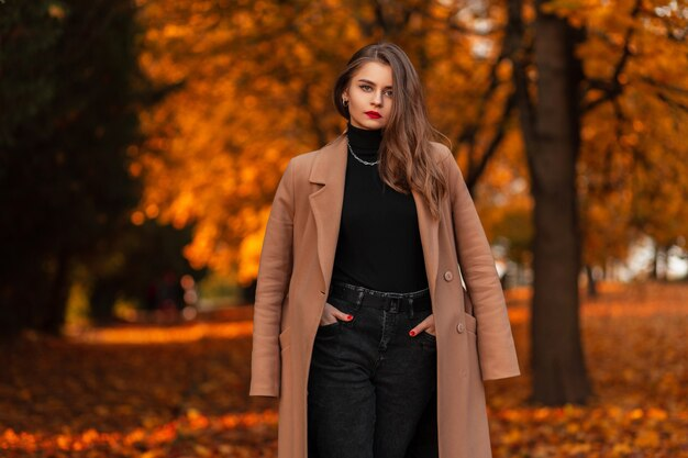 La donna con le labbra rosse in un cappotto beige alla moda con un maglione nero cammina in un parco autunnale con fogliame arancione brillante. stile femminile casual all'aperto
