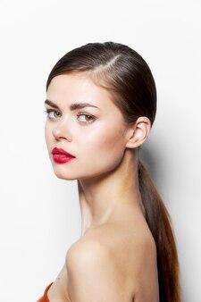 Donna con i capelli lunghi di sguardo attraente delle spalle nude delle labbra rosse