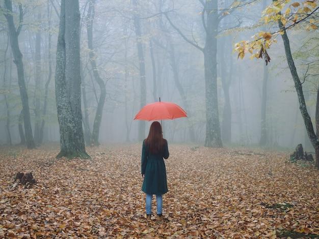 Donna con l'ombrello rosso nella nebbia di autunno foglie gialle aria fresca