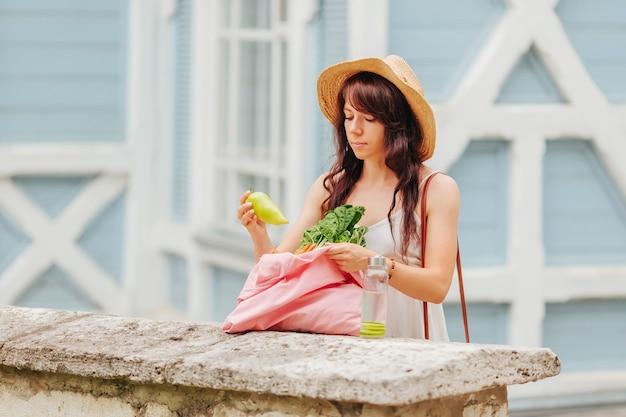 Donna con borraccia riutilizzabile e borsetta in bambù, borsa della spesa in cotone con verdure.