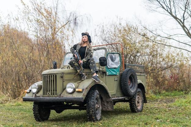 Donna con fucile in posa su auto militare