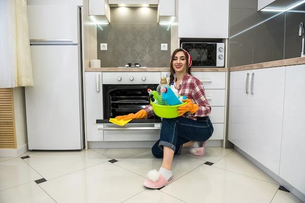 Donna con guanti di gomma e disinfettante lava il pavimento in cucina.