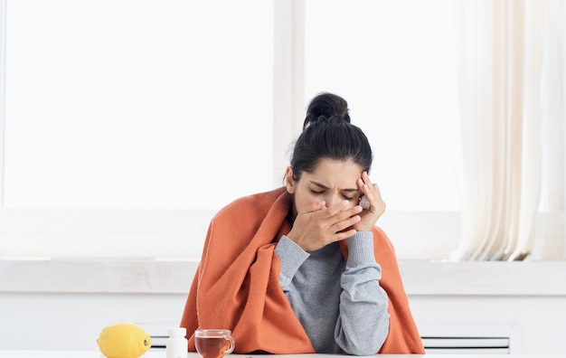 Una donna con il naso che cola si siede al tavolo con pillole di limone giallo e una tazza di tè. foto di alta qualità