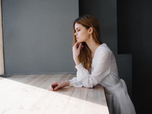 Donna con abito bianco espressione facciale triste vicino alla finestra di lusso