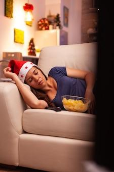 Donna con cappello da babbo natale che dorme sul divano dopo aver visto un film di intrattenimento invernale