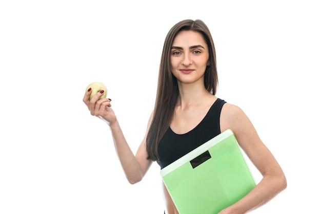 Donna con bilancia e mela isolata su bianco