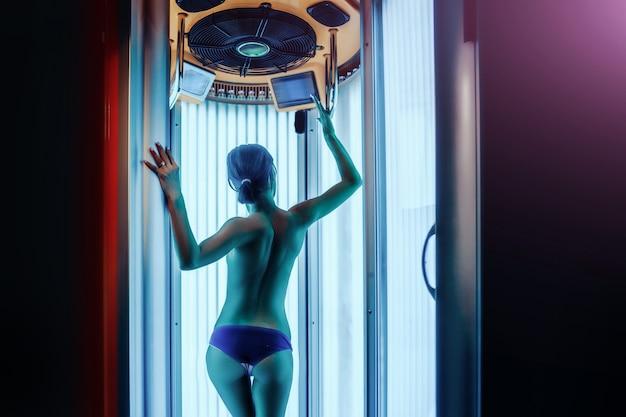 La donna con il corpo sano nudo sexy nel salone della stazione termale del solarium ha bello spazio della copia delle natiche e della schiena