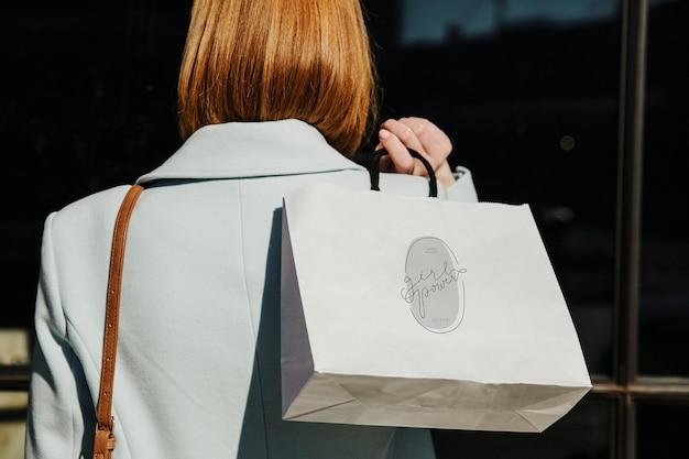 Donna con una borsa della spesa dopo una spesa sfrenata