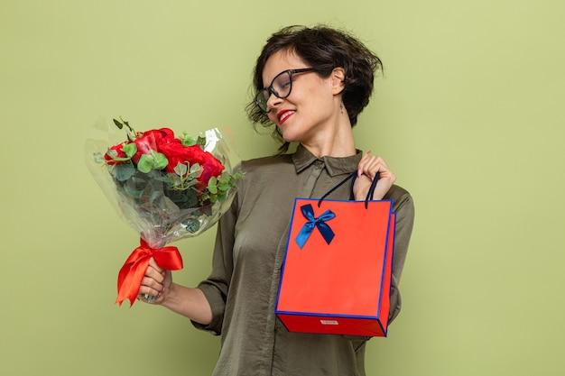 Donna con i capelli corti che tiene un mazzo di fiori e un sacchetto di carta con regali felici e contenti sorridenti che celebrano la giornata internazionale della donna l'8 marzo in piedi su sfondo verde
